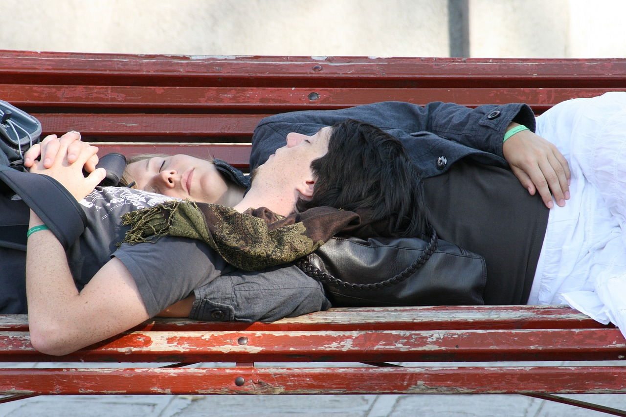 couple sleeping on a bench