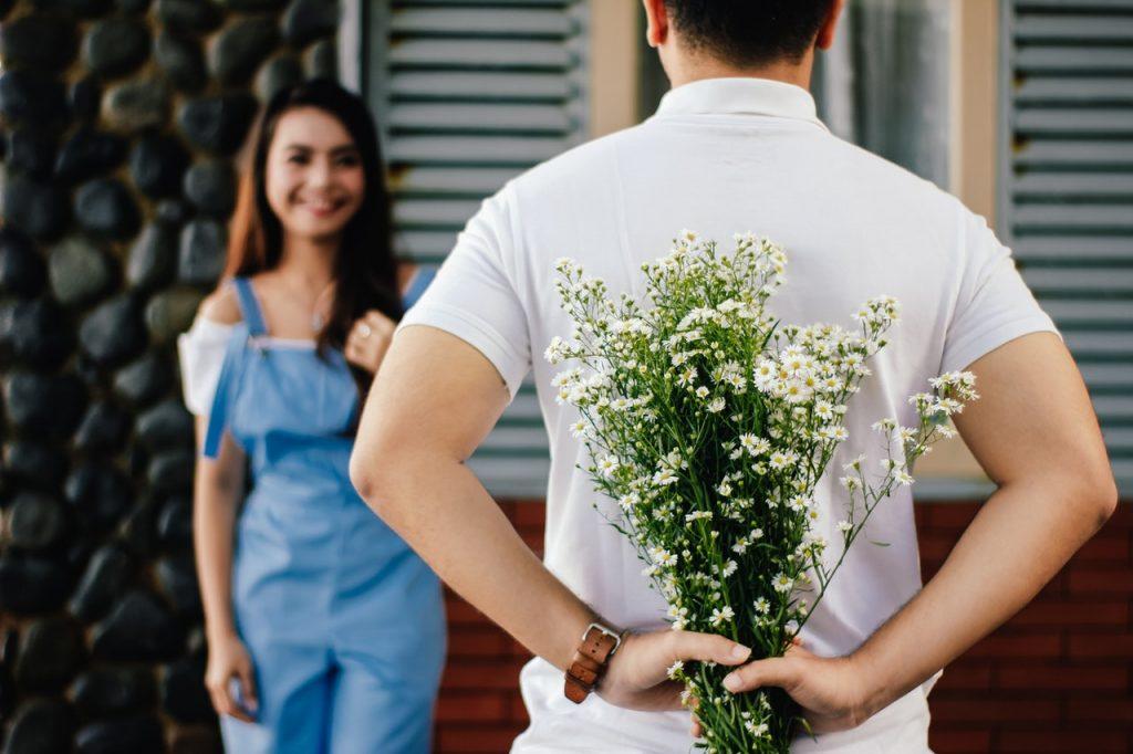 man giving woman flowers