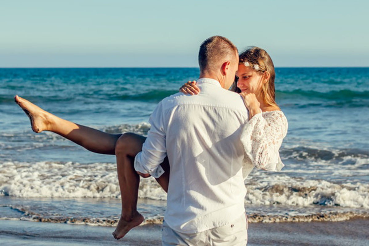 man carrying woman on the beach