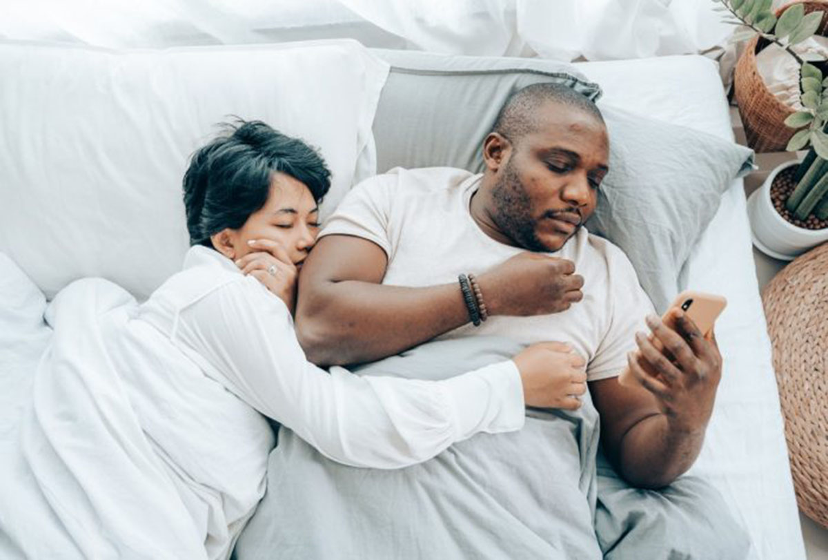 man on his cell phone in bed